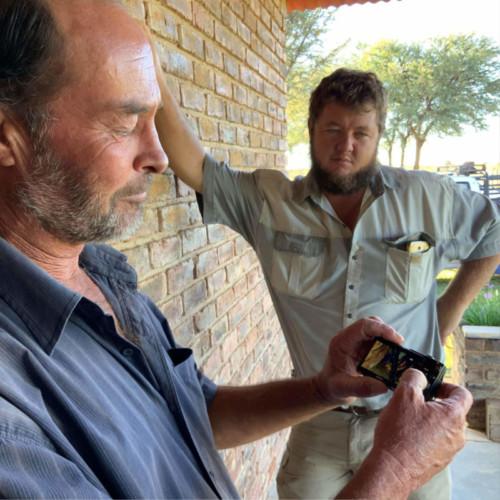 """Kobus Cloete van Tosca wys vir my en Koos du Plessis die ou skilpadwyfie wat hy 'Oumatjie' gedoop het, wat op sy plaas kom water soek het. """"Wanneer sy hier aankom om onder die tenk 'n lafenissie te soek, dan reën dit gewoonlik binne dae. Sy l bring altyd vir my goeie tyding,"""" vertel Kobus."""